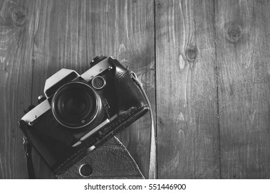 retro film camera on wooden table. black and white photo