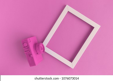 Retro film photo camera colored in pastel pink with photo frame minimal abstract creative concept. Place for photo adding.