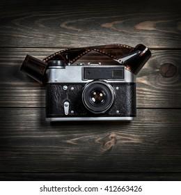 Retro film photo camera on the wooden background.