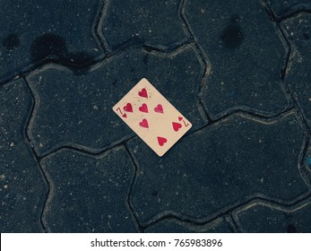 Retro filter effect - Discarded 7 of hearts playing card on dirty cement brick road