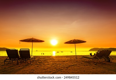 Retro filtered picture of beach chairs and umbrellas on sand at sunset. Concept for rest, relaxation, holidays.