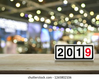 Retro flip clock with 2019 text on wooden table over blur light and shadow of shopping mall, Happy new year cover concept
