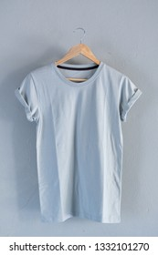 Retro fold blue cotton T-Shirt clothes mock up template on grunge white wood background concept for retail dress shop backdrop, Blank flat lay vintage grey wooden plain laundry advertising