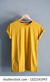 Retro fold Yellow cotton T-Shirt clothes colorful mock up template on grunge white wood background concept for retail dress shop backdrop, Blank flat lay vintage grey wooden plain laundry advertising
