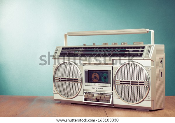 Retro ghetto blaster cassette tape recorder on table in front mint green background