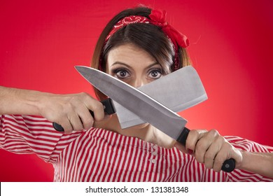 retro girl looking between two kitchen knives on a red background