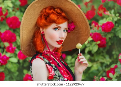 Retro girl with red lips in a dress with a print of roses with yellow lollipop on summer background. Young redhead model in a hat on a background of a bush of roses. Stylish woman. Sweet lollipop
