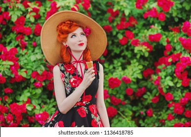Retro girl with red lips in a dress with a print of roses with ice cream on summer background. Young redhead model in a hat on a background of a bush of roses. Stylish woman. Sweet ice cream