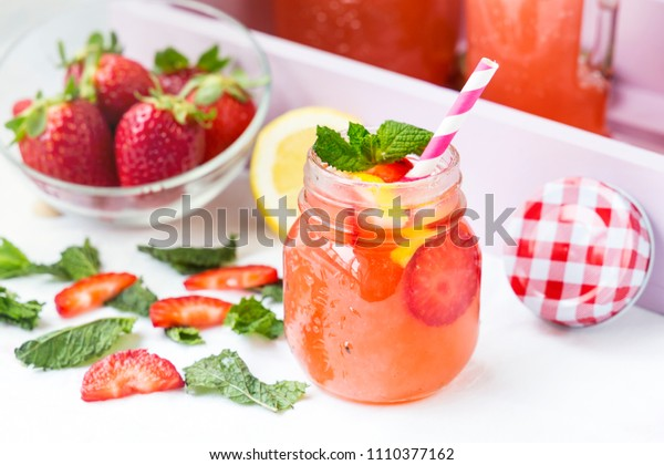 Retro glass jar of detox water with strawberries, lemon and mint