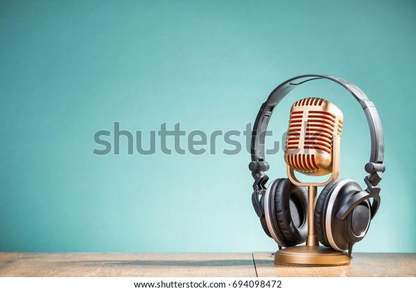 Micrófono retro dorado y auriculares en fondo de fondo de agua con gradiente frontal de mesa. Foto filtrada de estilo antiguo