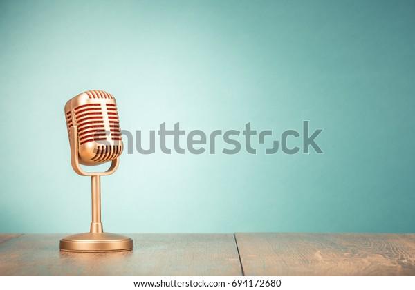 Retro goldenes Mikrofon für Pressekonferenz oder Interview auf Tisch-Vorderseite Farbverlauf-grüner Hintergrund. Vintage altes gefiltertes Foto