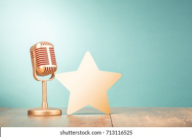 Retro golden microphone and star shape on wooden table front gradient mint green background. Vintage instagram old style filtered photo