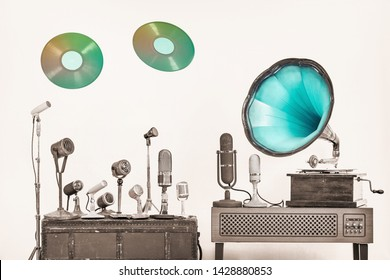 Retro gramophone phonograph turntable with mint blue horn, old antique microphones, two flying multicolor LP vinyl record discs. Nostalgia music concept. Vintage style filtered sepia photo