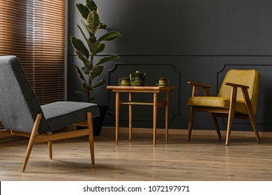 Retro green teapot and cups on a wooden side table and comfortable armchairs in a classy dark apartment interior with black wall