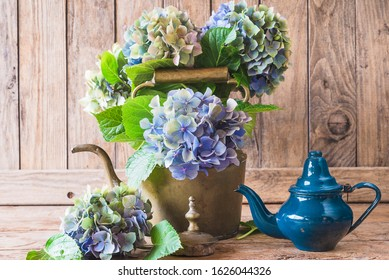 Retro greeting card. Bouquet of blue hydrangea flowers in vintage teapot an wooden background. Sunlight, close up