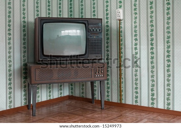 Retro grunge tv against wallpaper wall.
