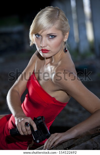 Retro gun woman lying on the wooden box in old fabric ruins