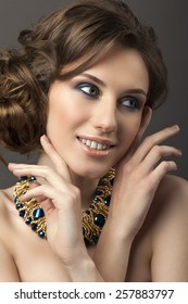 Retro hairstyle. Beautiful Brunette Woman. Fashion portrait with jewerly.On gray background.Hands near her face.