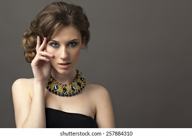 Retro hairstyle. Beautiful Brunette Woman. Fashion portrait with jewerly.On gray background.Hand near her face.