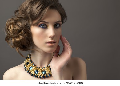 Retro hairstyle. Beautiful Brunette Woman. Fashion portrait with jewerly.On gray background.Hand near her neck.