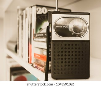Retro handheld transistor radio on shelf with cassettes-Vintage photography-Conceptual. Warm soft  70's look.