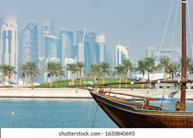 Retro historical boat with blurred panoramic view of modern skyline of Doha and green palms on background