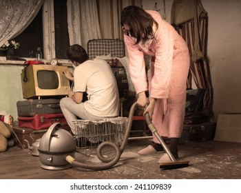 Retro housewife in her dressing gown and slippers cleaning a messy living room with a vintage vacuum cleaner while her husband watches television on an old TV set, aged style toning