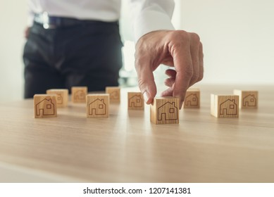 Retro image of businessman arranging wooden blocks with house icon on them on office desk.