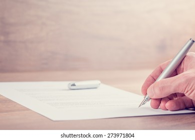Retro image of businessman hand signing contract or other important documents on a rustic wooden desk.