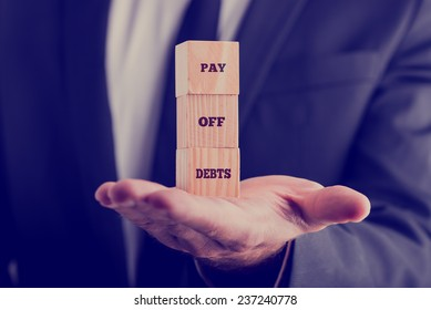Retro image with a businessman holding a stack of three wooden cubes balanced on his palm displaying text Pay off debts.