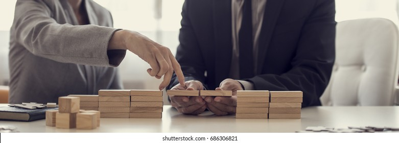 Retro image of businesspeople solving problems by building bridges with wooden blocks to span a gap for partner to walk her fingers across in a conceptual image.