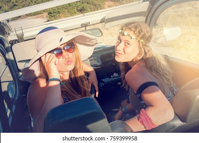 Retro image of girl friends in a car at sunset