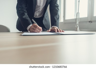 Retro image of a lawyer signing legal document or testament with fountain pen.