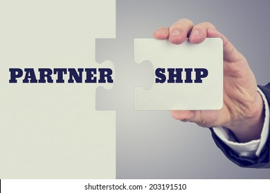 Retro image of male hand holding piece of puzzle to create a word Partnership. Concept of importance of teamwork and cooperation.