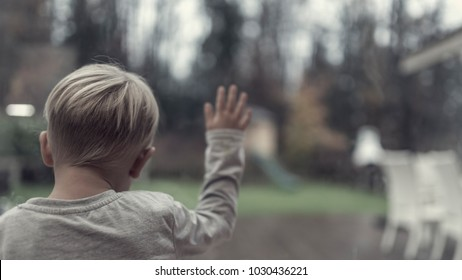 Retro image of one young child in front of a window looking longingly outdoors at the garden.