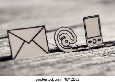 Retro image of At sign, mail and phone symbols outlined with black stuck in between a crack in the wooden surface.