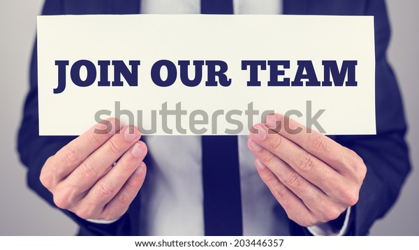 Retro instagram style image of businessman holding white card with Join our team sign.
