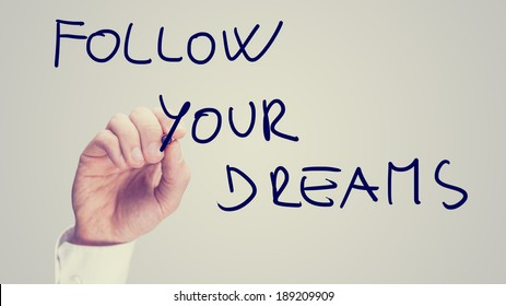 Retro instagram style image of a male hand writing motivational message Follow your dreams on virtual board.