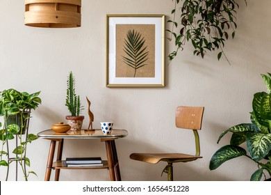 Retro interior design of living room with stylish vintage chair and table, plants, cacti, personal accessories and gold mock up poster frame on the beige wall. Elegant home decor. Template.  - Shutterstock ID 1656451228