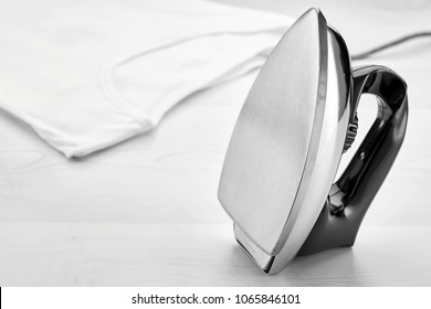 Retro iron positioned vertically and a white t-shirt on a table. Concept of ironing housework.
