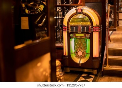 Retro jukebox in the corner of a restaurant by a set of stairs.