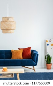 Retro lampshade above a simple, wooden coffee table on a navy blue rug in a colorful living room interior with pillows on a couch. Real photo.