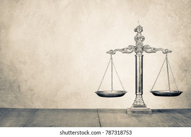 Retro law scales on wooden desk front concrete wall background. Symbol of justice. Vintage old style sepia photo