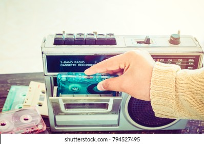 Retro lifestyle - Woman hand holding tape cassette with cassette player and recorder for listen music - vintage color tone effect.