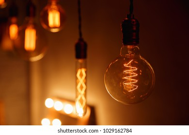 Retro light bulb with unusual spiral. Edison lamp on black background.