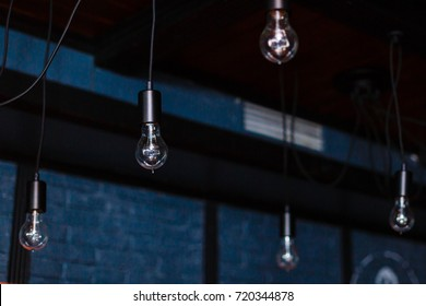 Retro light bulbs hang in interior with white brick wall background. light bulbs hanging on brick wall backdrop