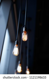 Retro light bulbs with weak glow hanging on wires to the ceiling.