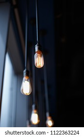Retro light bulbs with weak glow hanging on wires to the ceiling. A place where people rest, it looks like a coffee house.