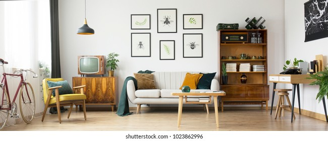 Retro living room design with old television, cabinet and radio along with work area with typewriter - Shutterstock ID 1023862996