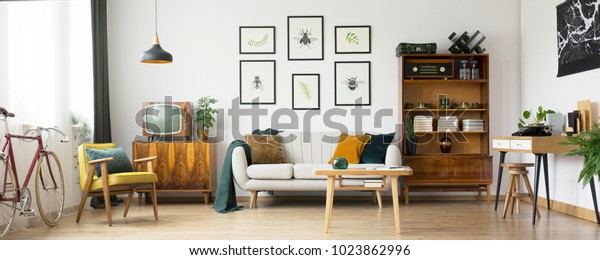 Retro living room design with old television, cabinet and radio along with work area with typewriter